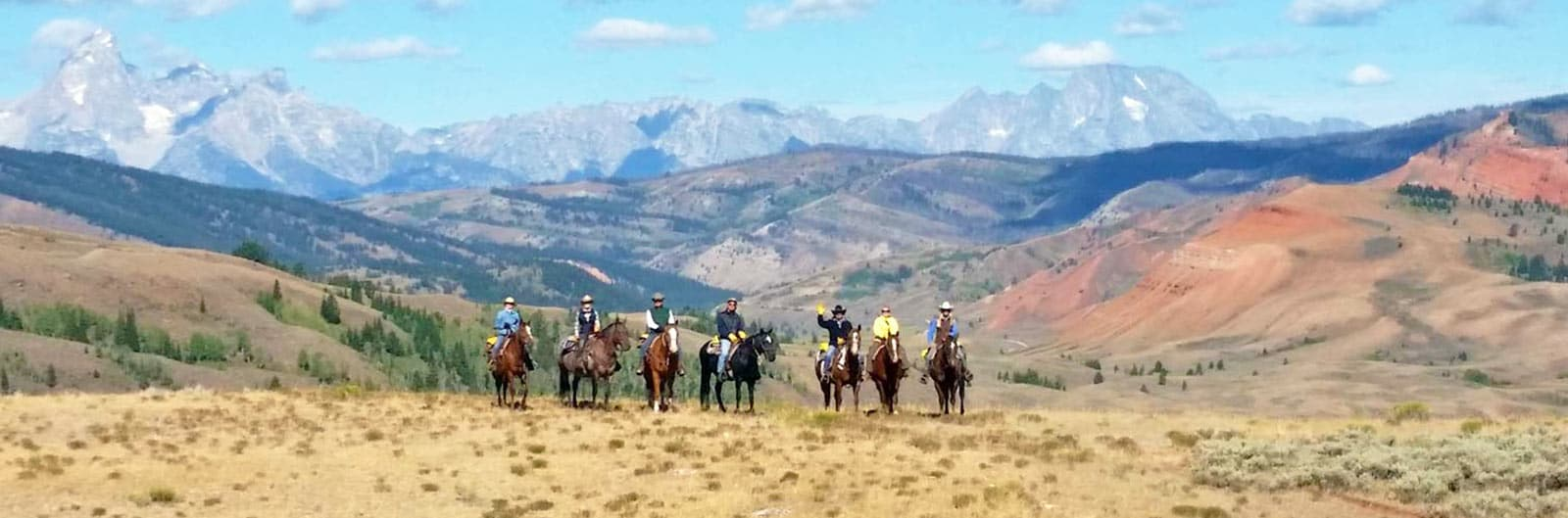 Cowboys with Tetons in distance