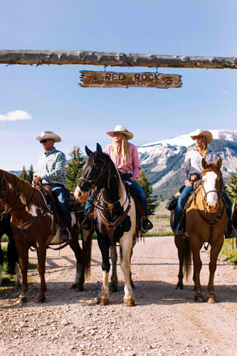 Three people on horseback beneath a The Red Rock Ranch rustic sign